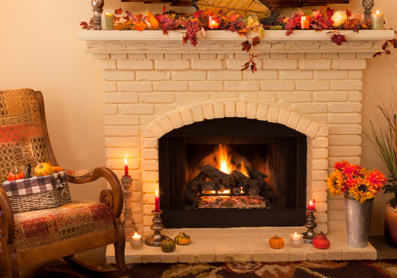A light yellow brick old fashioned fireplace with arched opening has a roaring fire with logs and is decorated on the mantel and hearth with Thanksgiving or Autumn decorations. Candles are lit on candlesticks and fall leaves with gourds and grapes help decorate. Sunflowers and mums also fill tins and baskets on the carpeted floor. A rocking chair sits in the corner next to the fireplace in the left corner of this horizontal image. There is copy space in the left top corner.